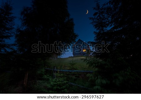 Wooden rural house on the green hill between of big carpathian spruce trees at twilight hour. New moon over it. - stock photo