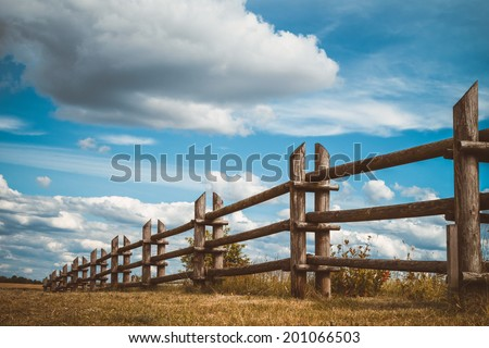 wooden rustic fence in village and blue sky with clouds - stock photo