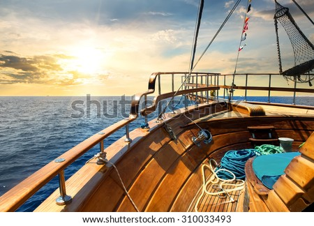 Wooden sailboat in the sea at sunrise - stock photo
