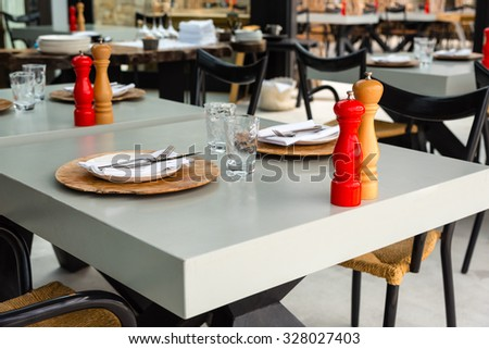 wooden salt and pepper mills on nicely set tables - stock photo