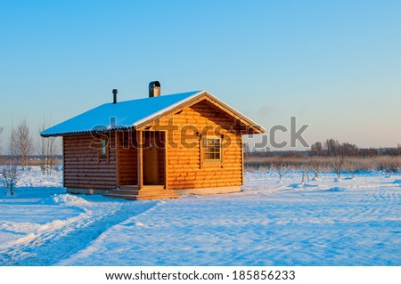 wooden saun house in snow and frozen landscape. russian winter - stock photo