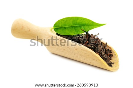 Wooden scoop with black tea with leaf isolated on white  - stock photo