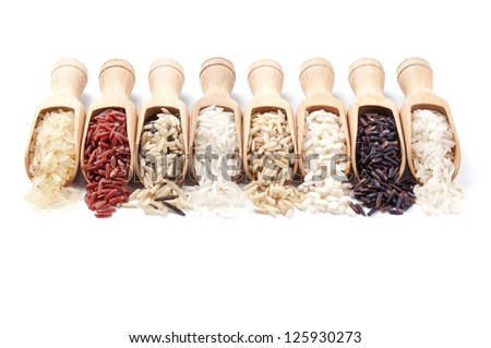 Wooden scoops with different rice types scattered from them on white background - stock photo