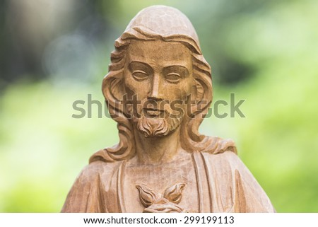 Wooden sculpture of Jesus Christ with burred nature background, close up - stock photo