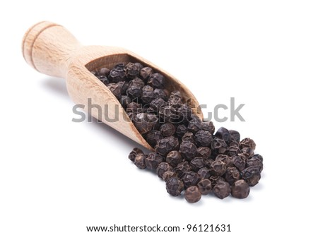 Wooden shovel with black peppercorn scattered from it - stock photo