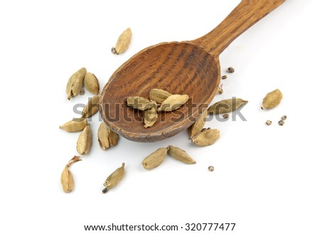 wooden shovel with cardamom pods scattered from it - stock photo
