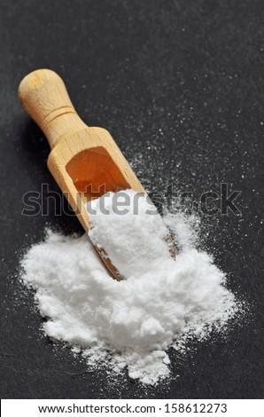 Wooden shovel with sodium bicarbonate on black background - stock photo