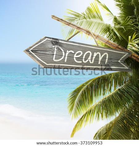 Wooden sign Dream on tropical white sand beach summer background. Lush tropical foliage and sunshine. Blue ocean at perfect day. No people. - stock photo