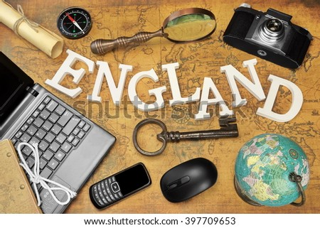Wooden Sign England, Laptop, 35mm Photo Camera, Key,  Globe, Magnifier, Compass, GSM Phone, Bell, Computer Mouse And Letter On The Old Map, Flat Lay, Top View - stock photo