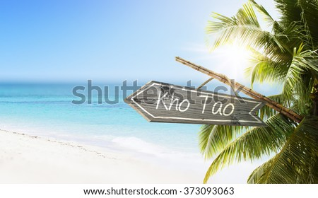 Wooden sign Kho Tao on tropical white sand beach summer background. Lush tropical foliage and sunshine. Blue ocean at perfect day. No people. - stock photo