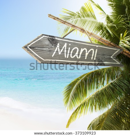 Wooden sign Miami on tropical white sand beach summer background. Lush tropical foliage and sunshine. Blue ocean at perfect day. No people. - stock photo