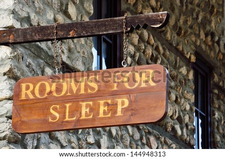 Wooden sign on the wall of the motel - stock photo