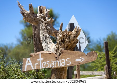 Wooden sign post on dried cactus with Artesanias written in Spanish or crafts in English, blurred blue and green nature background. Cafayate, Salta Province. Argentina - stock photo