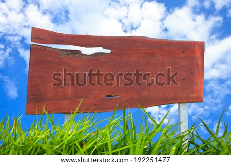 Wooden sign with green grass isolated on sky background - stock photo