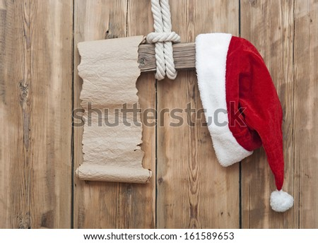 wooden sign with Santa's hat and blank paper scroll on a wooden background  - stock photo