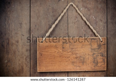 Wooden signboard with rope hanging on grunge planks background - stock photo