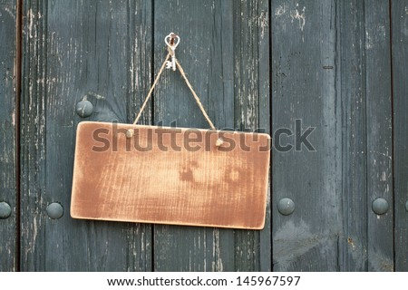 Wooden signboard with rope hanging on planks background - stock photo
