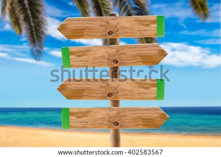 wooden signpost in the meadow with copyspace on the beach and palms - stock photo