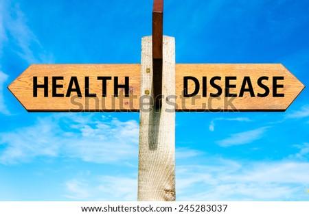 Wooden signpost with two opposite arrows over clear blue sky, Health versus Disease messages  - stock photo