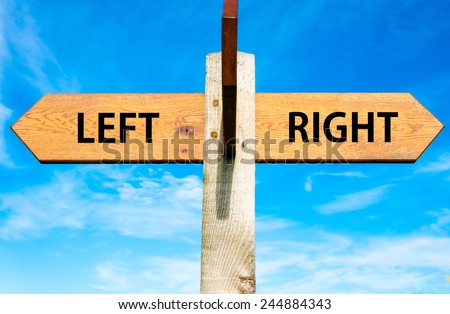 Wooden signpost with two opposite arrows over clear blue sky, Left versus Right messages, Choice conceptual image - stock photo