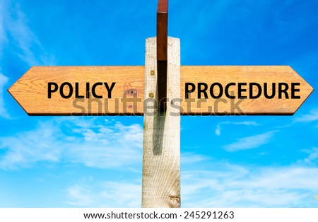 Wooden signpost with two opposite arrows over clear blue sky, Policy versus Procedure messages - stock photo