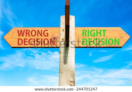 Wooden signpost with two opposite arrows over clear blue sky, Right Decision and Wrong Decision, Right choice conceptual image - stock photo