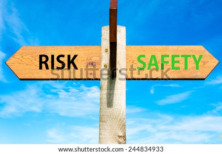 Wooden signpost with two opposite arrows over clear blue sky, Risk versus Safety messages, Right choice conceptual image - stock photo