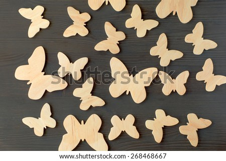 wooden silhouettes of butterflies on a black background - stock photo