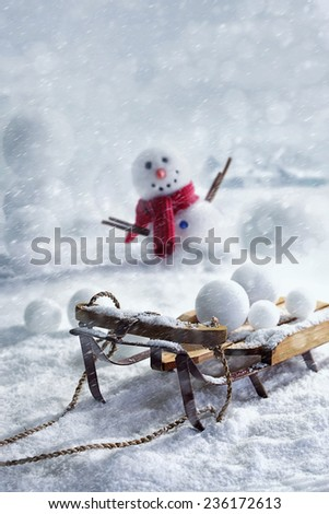 Wooden sleigh and snowballs with snowman and wintery background - stock photo