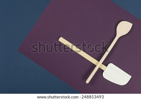 Wooden spatula and spoon arranged to overlap on a napkin over a blue background in a food preparation and baking concept, overhead view - stock photo
