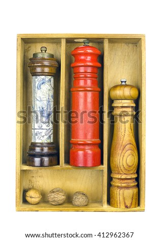 Wooden spice grinders in a wooden box with three walnuts - stock photo