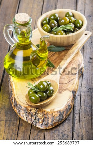 Wooden spoon and bowl with green olives and a jar with olive oil on a cutting board on the table of the kitchen - stock photo