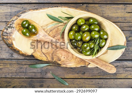 Wooden spoon and bowl with green olives on a cutting board on the table of the kitchen - stock photo