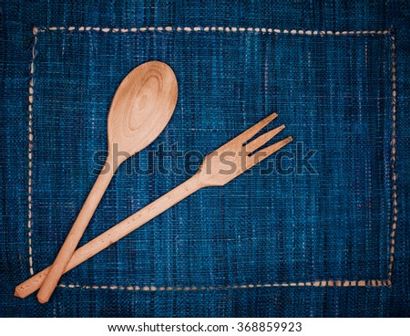 Wooden spoon and fork on blue placemat   - stock photo