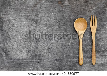 wooden spoon and fork on grunge wooded table background  - stock photo