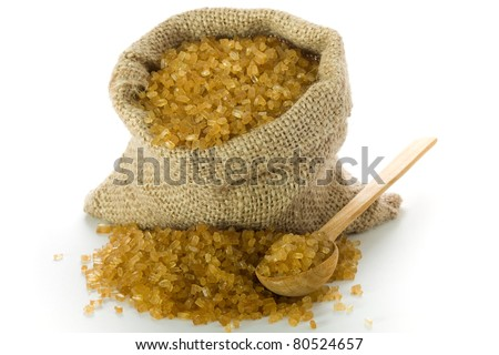 Wooden spoon and healthy cane sugar in small burlap - stock photo