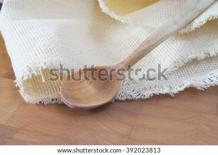 Wooden spoon and napkin on  chopping board - stock photo