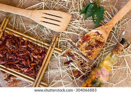 Wooden spoon, dried crushed chili red pepper and whole dried chili peppers on burlap background - stock photo