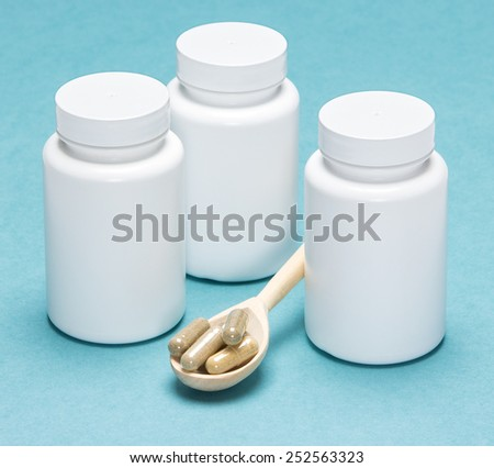 Wooden spoon filled capsules and white jars on a blue background - stock photo
