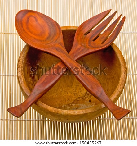 Wooden spoon, fork and basin on bamboo mat - stock photo