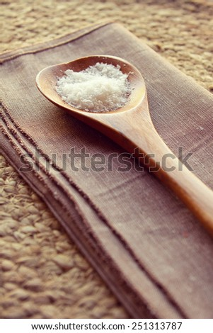 Wooden spoon full of sea salt flakes on linen napkin on rustic background - stock photo