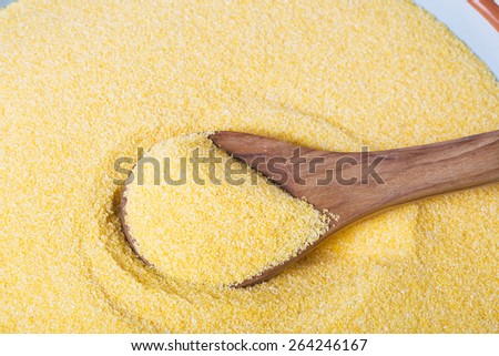 Wooden spoon in bowl of polenta - stock photo