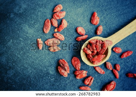 Wooden spoon of dried goji berries on black slate - stock photo