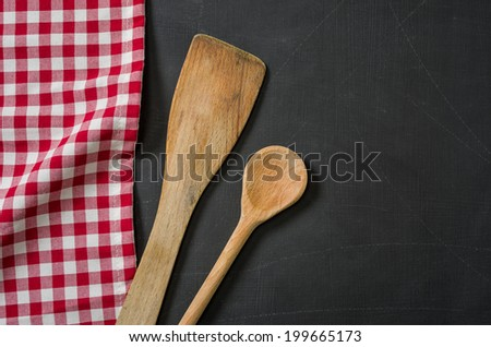 Wooden spoon on a blackboard with a red checkered tablecloth - stock photo