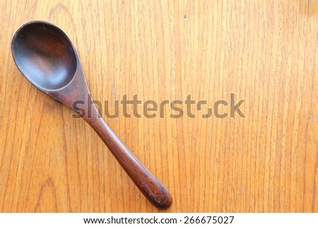 wooden spoon on wooden background - stock photo