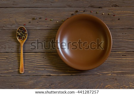 Wooden spoon with colored pepper lies on a rustic wooden table. Near earthenware dish - stock photo