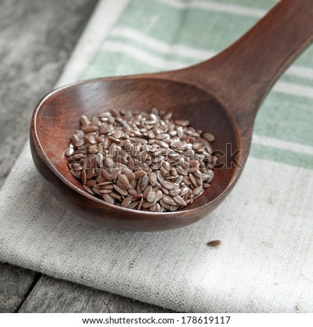 wooden spoon with flax seed placed on a wooden table - stock photo