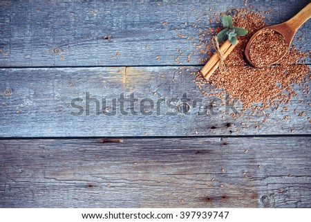 Wooden spoon with flax seeds, mint and cinnamon on a wooden background. - stock photo