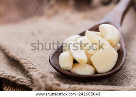 Wooden Spoon with Garlic (close-up shot) on vintage background - stock photo