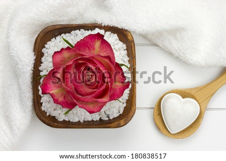 wooden spoon with heart shaped bath fizzer and white bath salt with red rose on top of it - stock photo